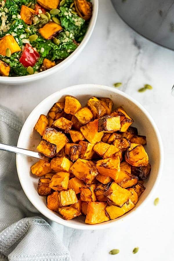 Bowl with air fryer butternut squash cubes and salad in background.