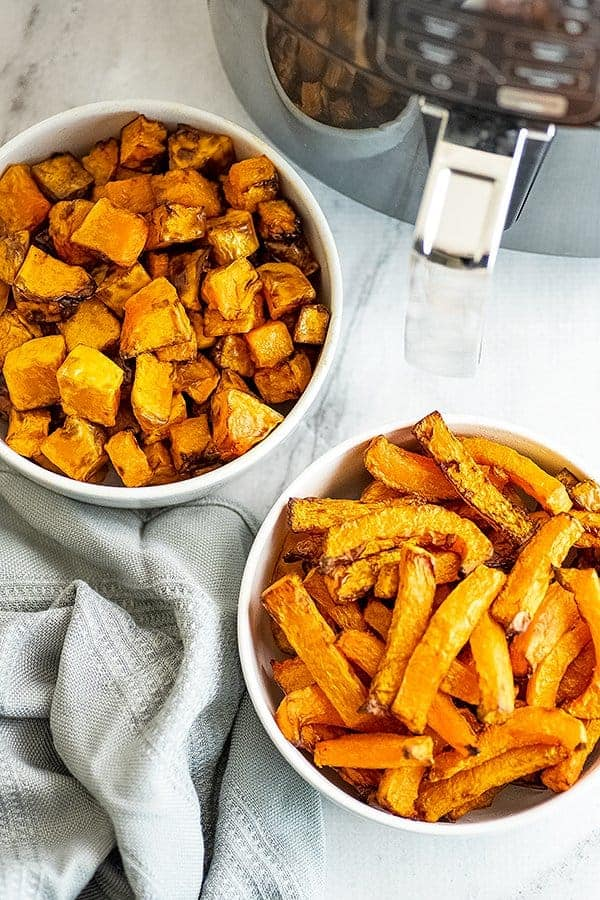 One bowl filled with air fryer butternut squash fries, other with cubes.