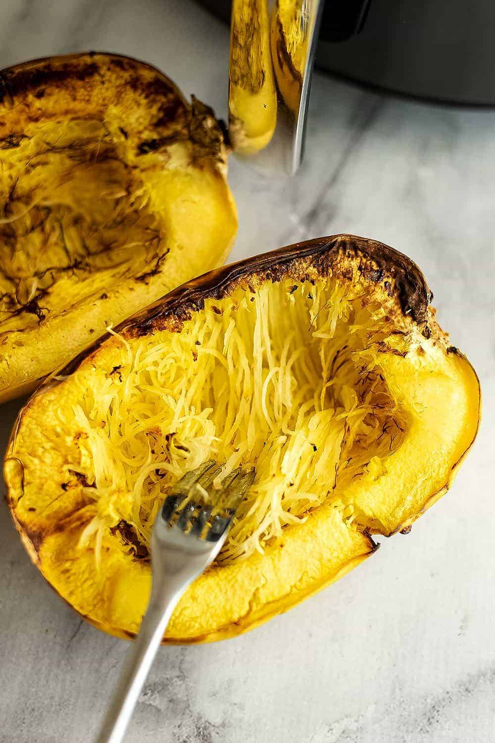 Fork dragging across spaghetti squash to release noodles.