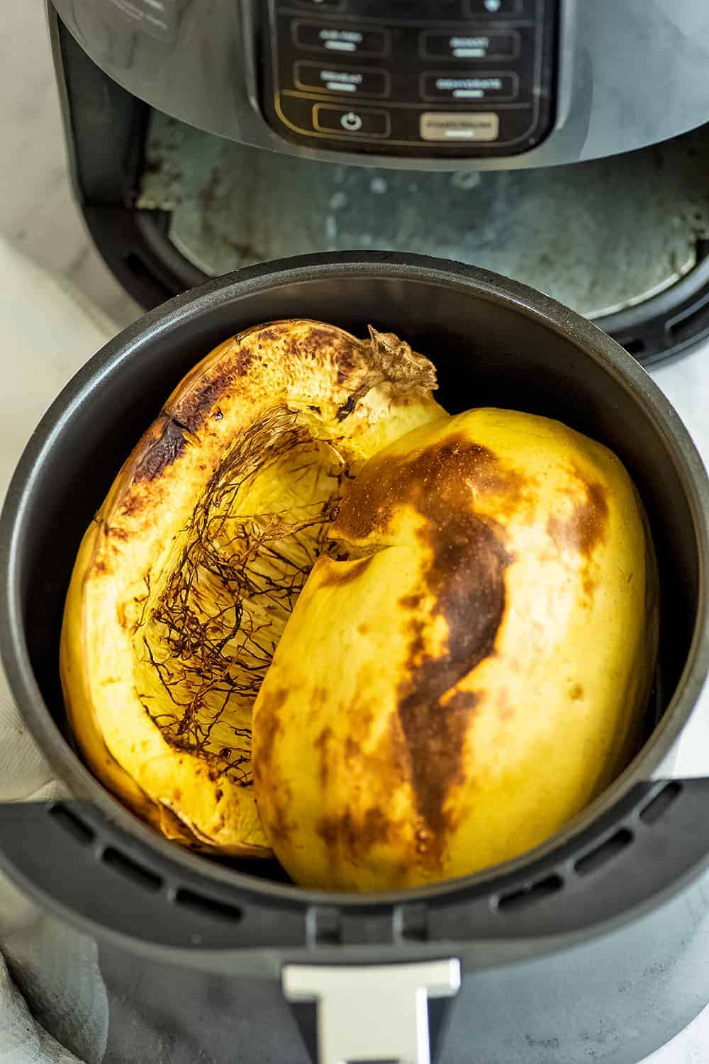 Spaghetti squash in air fryer basket after cooking.