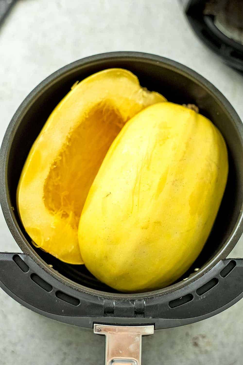 Spaghetti squash in air fryer basket before cooking.