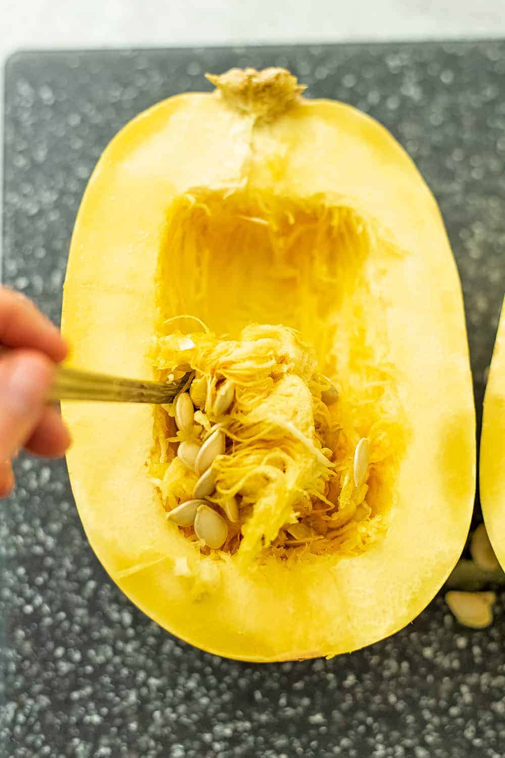 Spoon removing the seeds of a spaghetti squash.