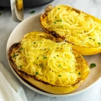 Spaghetti squash halves on a white plate after cooking.