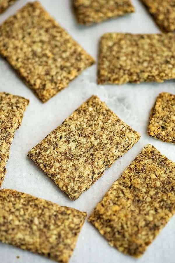 Handful of hemp almond flax crackers on a plate.