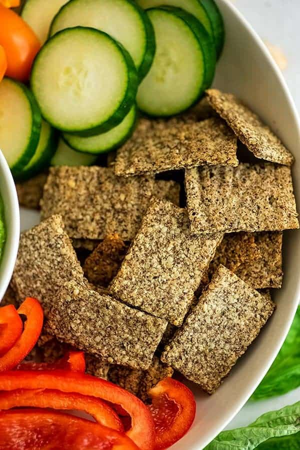 Almond flax crackers in a bowl with veggies.