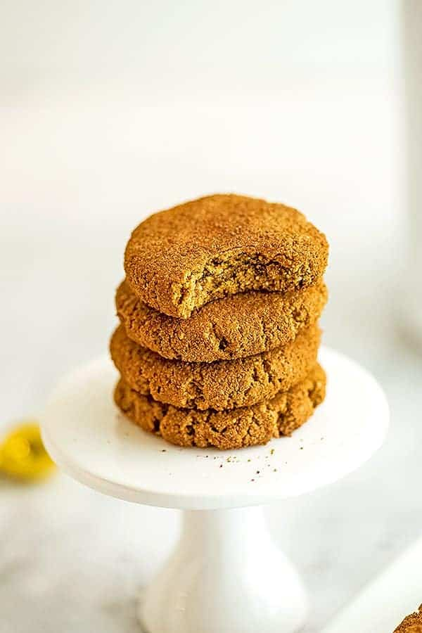 4 molasses cookies stacked on each other, the top with a bite taken out.