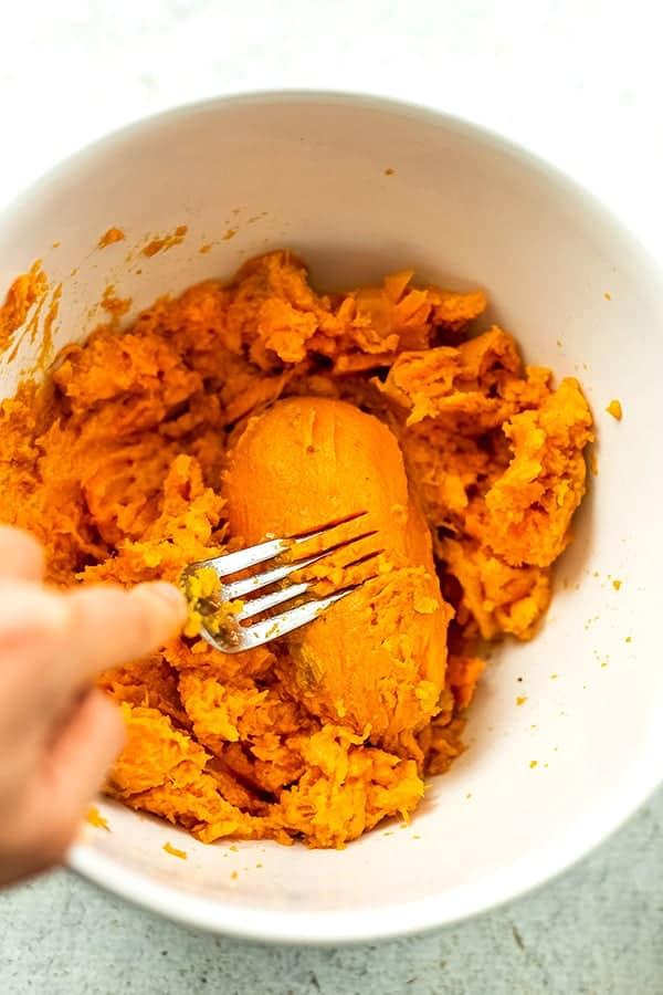 Fork mashing sweet potatoes in a bowl.