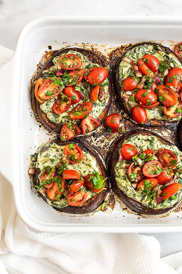 Four balsamic eggplant in a white baking dish.