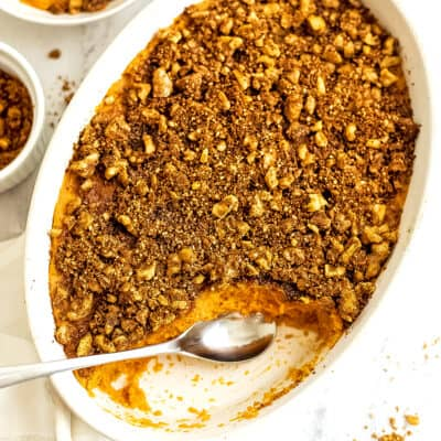 Spoon in a casserole dish filled with sweet potato casserole.