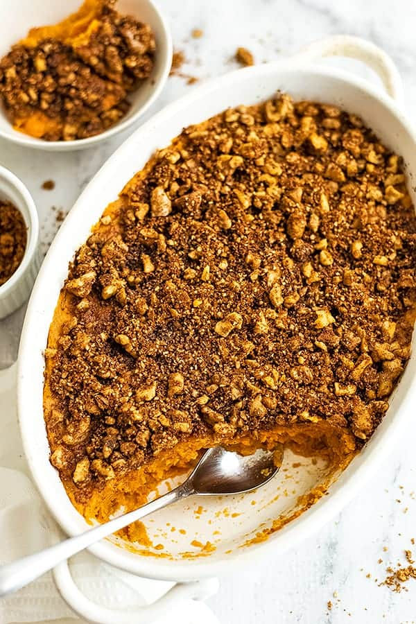 Oval casserole dish filled with sweet potato casserole with a spoon.