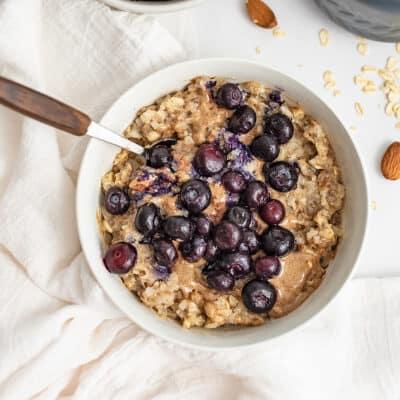 Bowl of blueberry almond oatmeal with wooden handle spoon.
