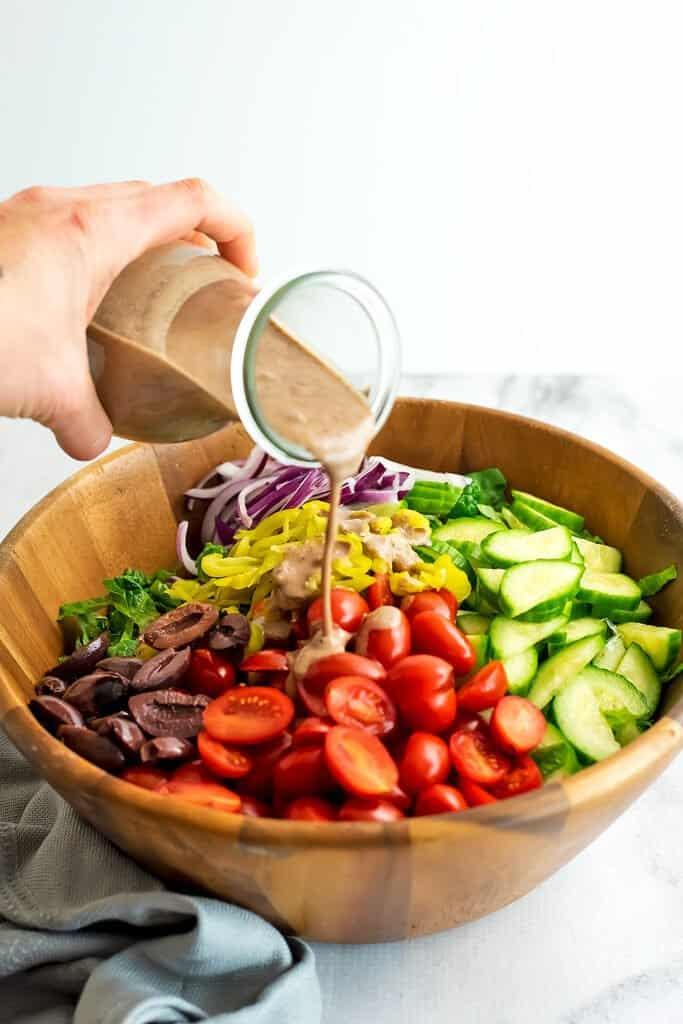 Kalamata olive dressing being poured over greek salad.
