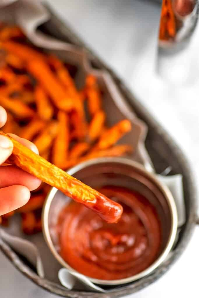 Air fryer carrot being dipped in ketchup.