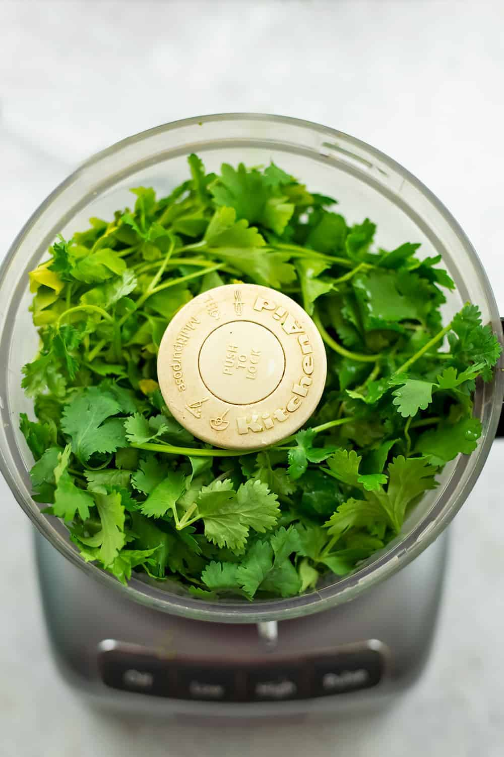 Food processor filled with cilantro and parsley.