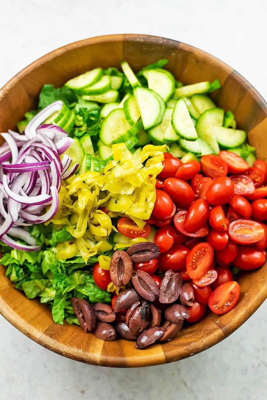 Chopped veggies on a greek salad before stirring.