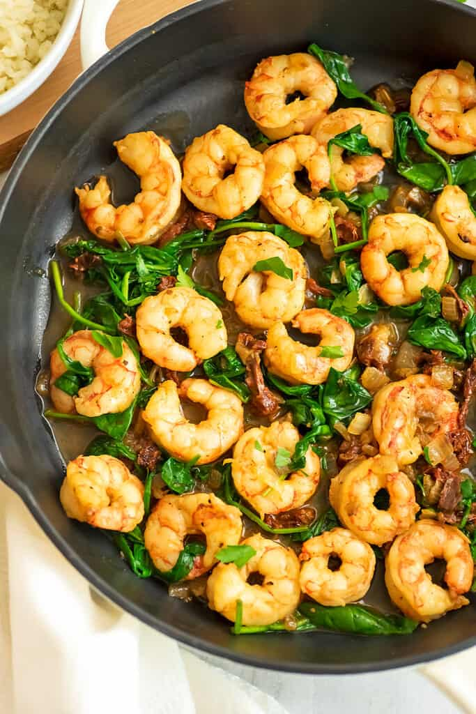 Skillet filled with sun dried tomato shrimp.