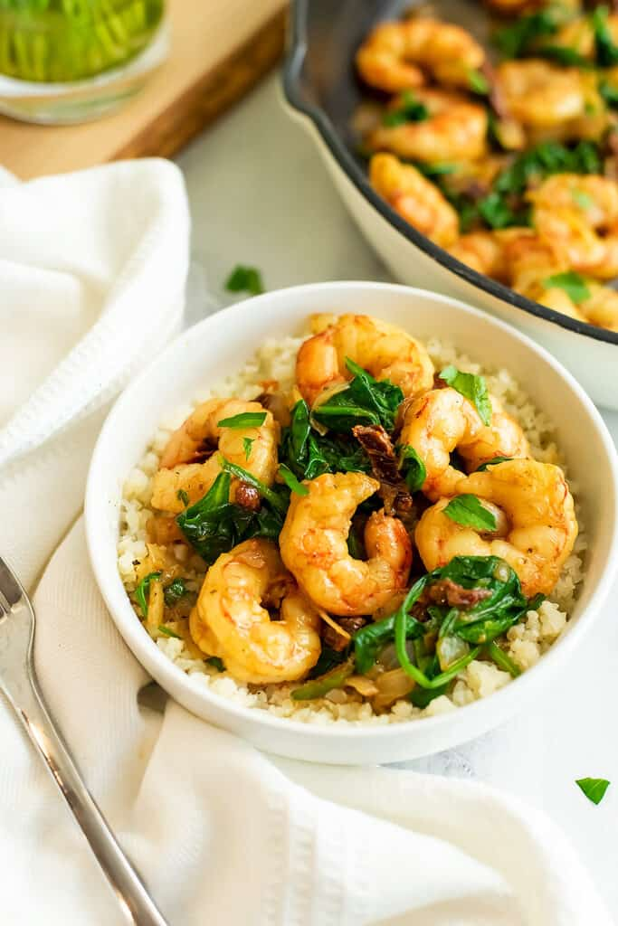 Bowl filled with sun dried tomato shrimp and cauliflower rice.