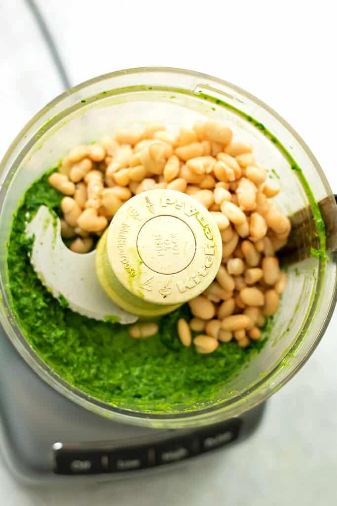 White beans and greens in the food processor before blending.