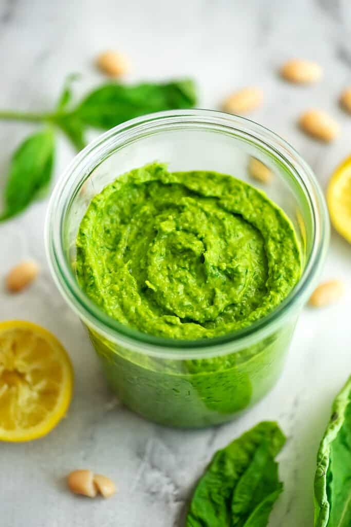 Glass jar filled with white bean pesto, lemons in the background.