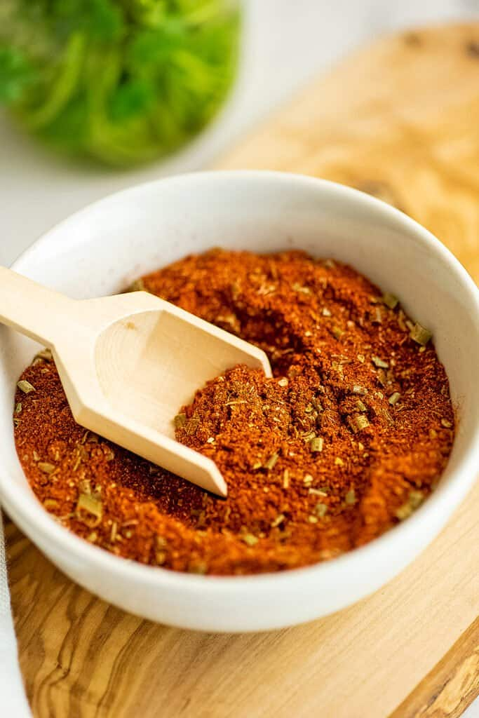 Wooden scoop in a bowl filled with Whole30 taco seasoning.