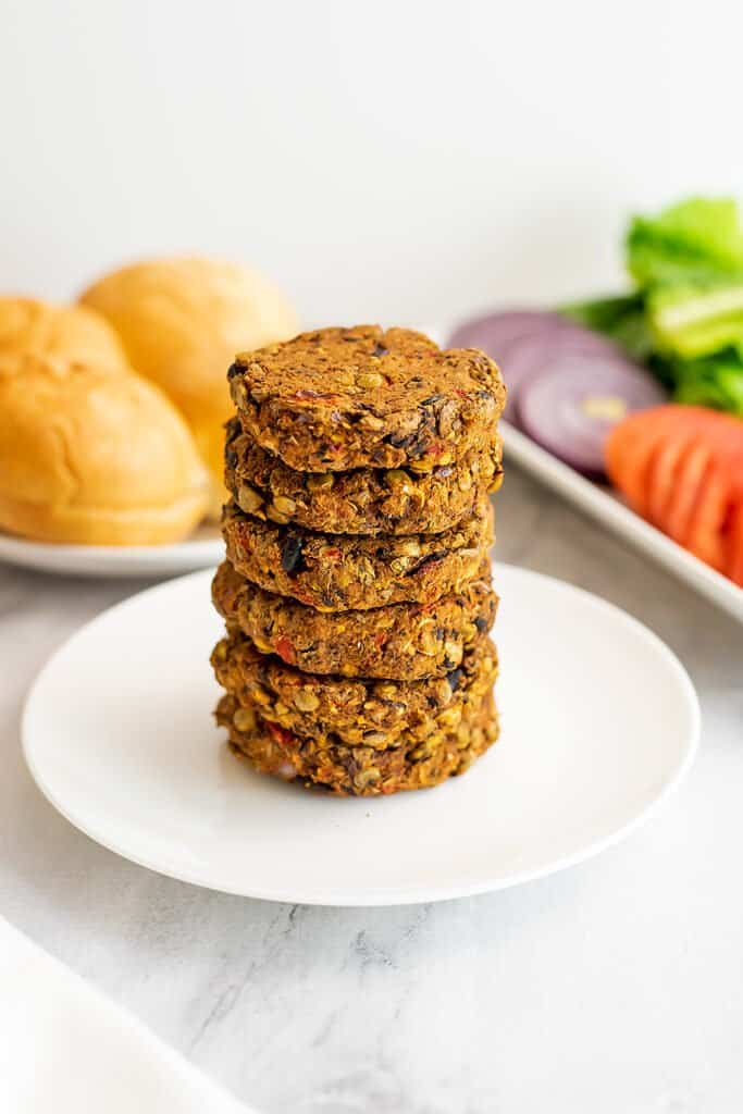 Black bean lentil burgers stacked on a white plate.