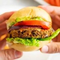 Hands holding a black bean lentil burger.