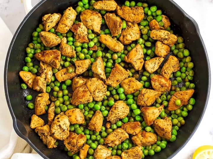 Cast iron skillet filled with chicken and peas.