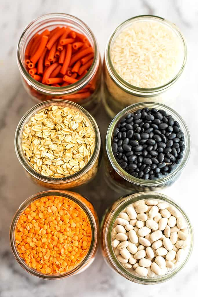 Glass jars filled with beans, rice and pasta.