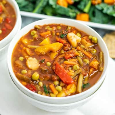 Bowl of vegetable soup with salad in background.