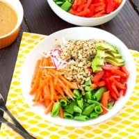 Bowl filled with fresh veggies, quinoa and peanut sauce.