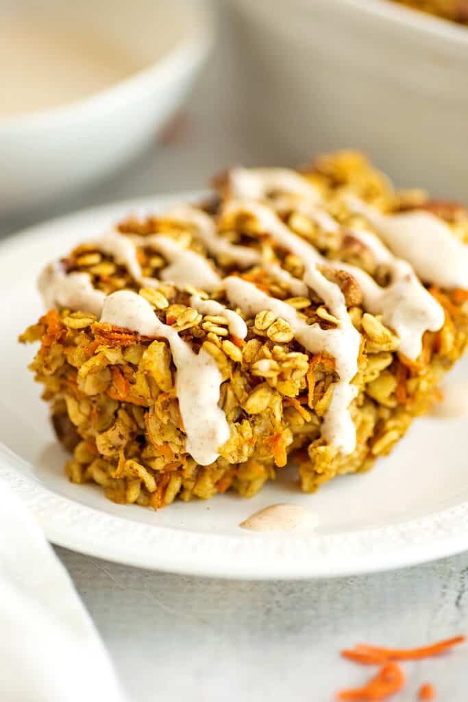Baked carrot cake oatmeal on a plate with maple frosting drizzle.