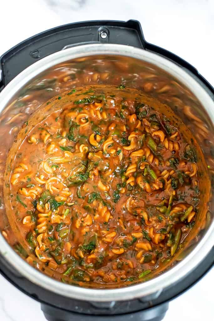 instant pot filled with chickpea pasta, marinara and spinach.