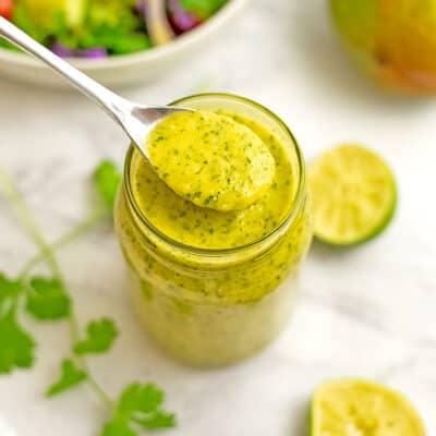 Spoon in a jar of mango dressing.