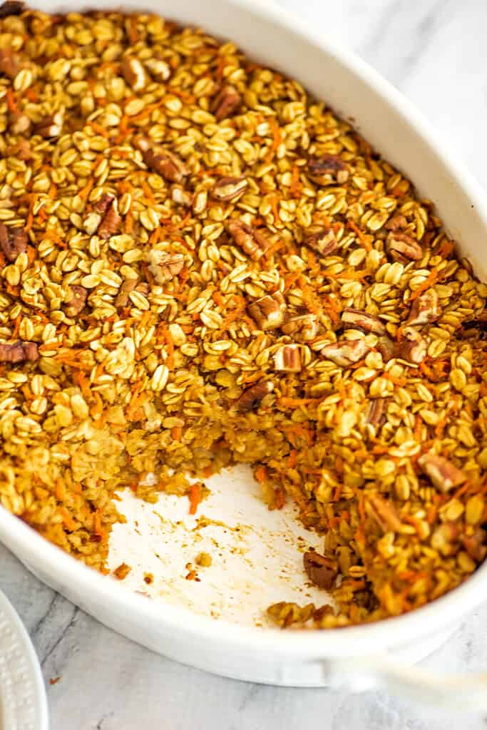 Baking pan full of baked carrot cake oatmeal with a piece removed.