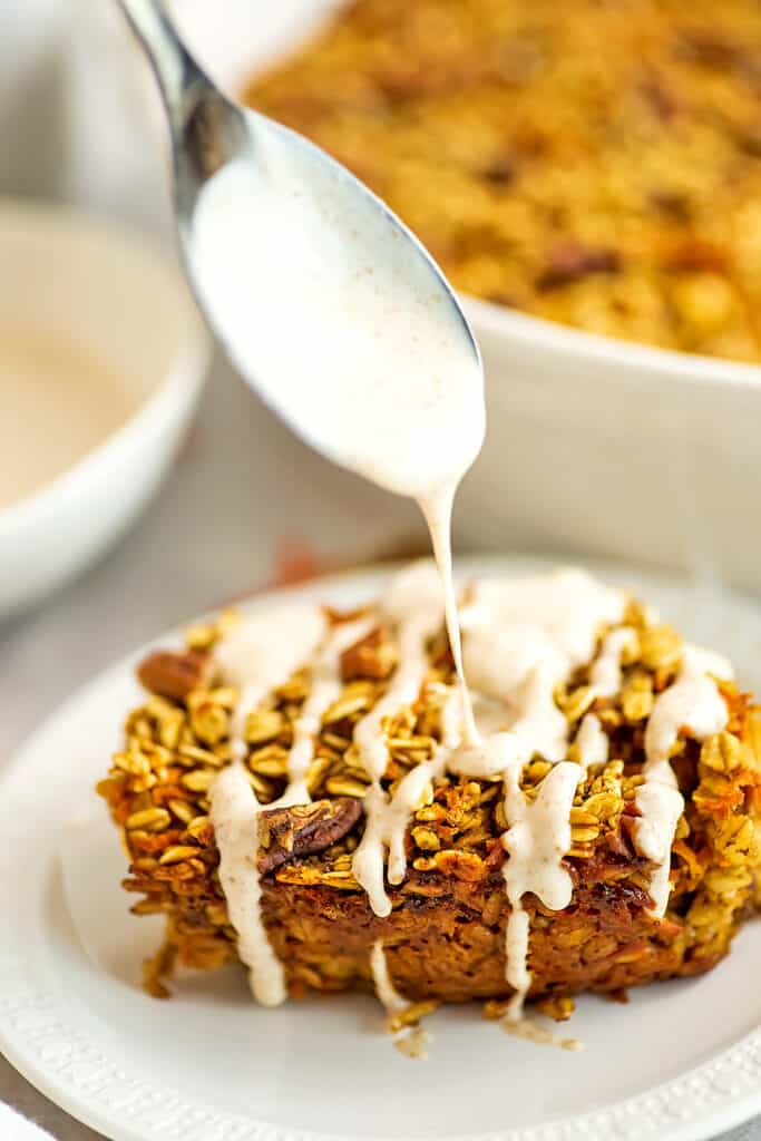 Spoon drizzling frosting over baked carrot cake oatmeal.