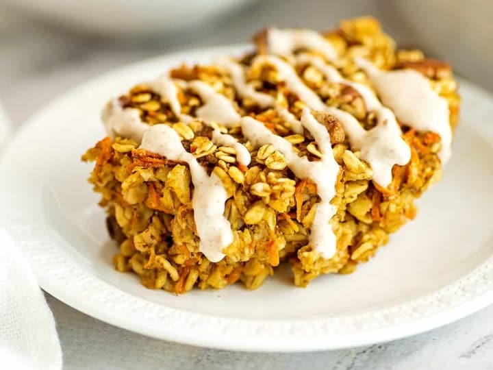 Oatmeal carrot cake with frosting on a white plate.