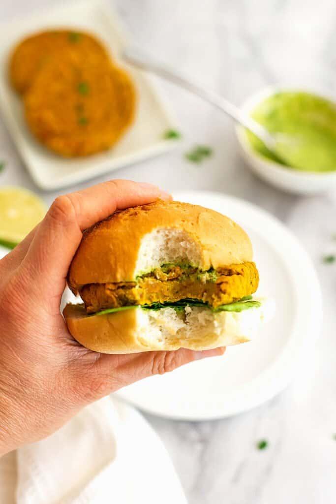 Hand holding a sweet potato lentil burger with a bite taken.