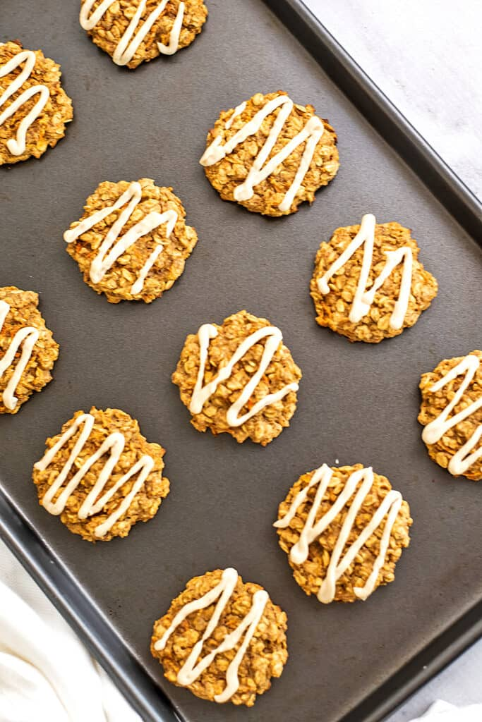 Baking sheet full of frosted carrot cake cookies.