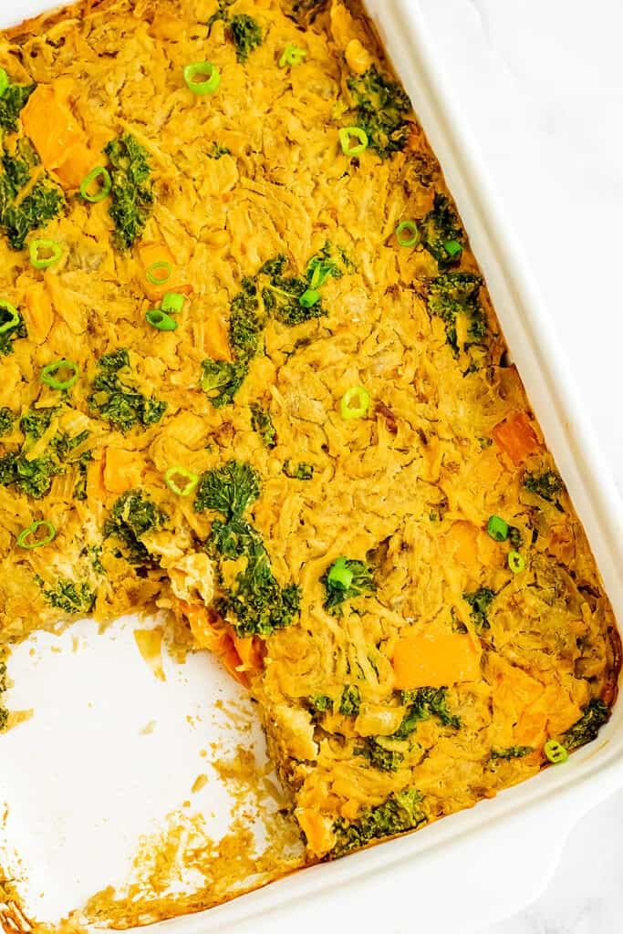 Vegetarian hash brown casserole with a serving removed.