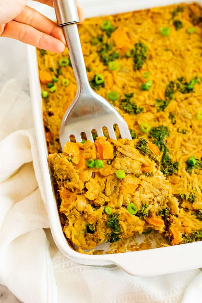 Vegan hash brown casserole being served with a silver spatula.