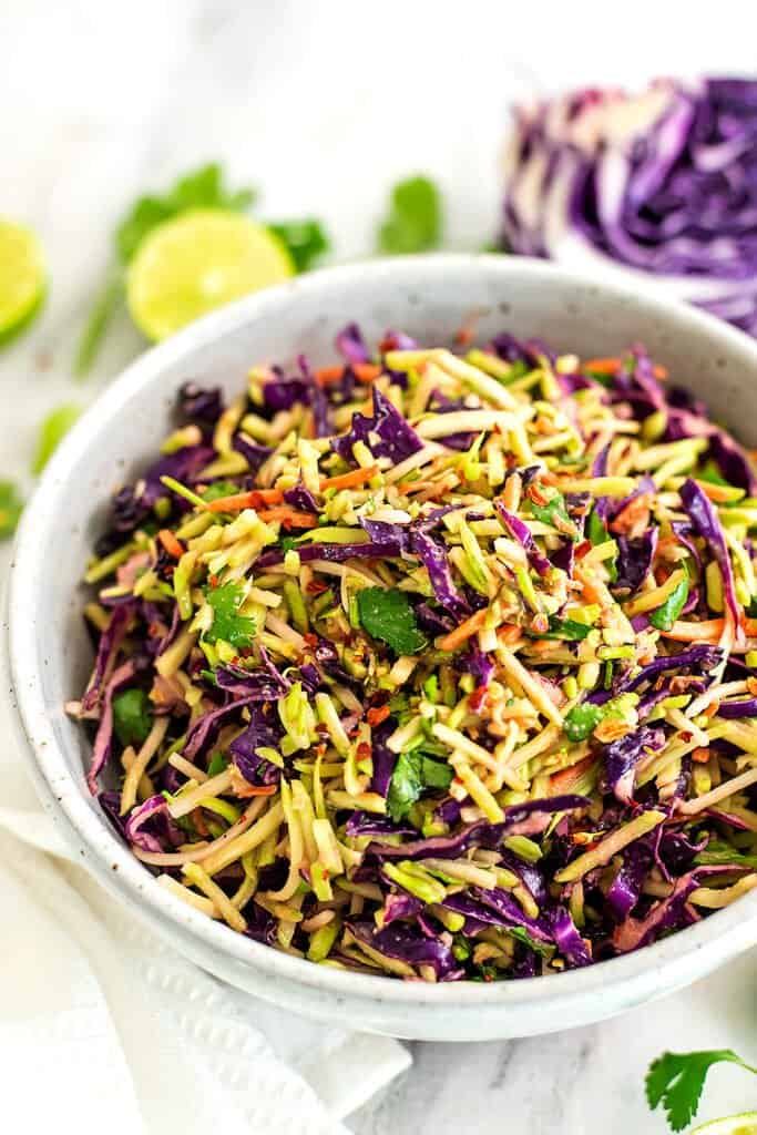 Asian Broccoli Slaw with limes and cabbage in background.