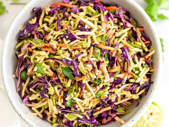 Asian broccoli slaw in a large bowl with red pepper flakes.