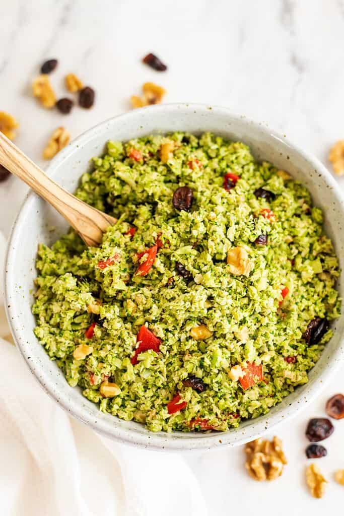 Spoon in a bowl of broccoli cranberry walnut salad.