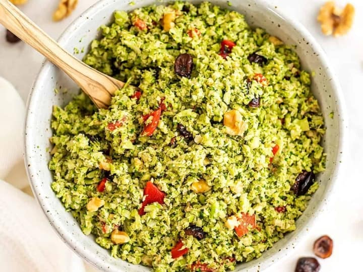 Riced broccoli salad with walnuts and cranberries in bowl.