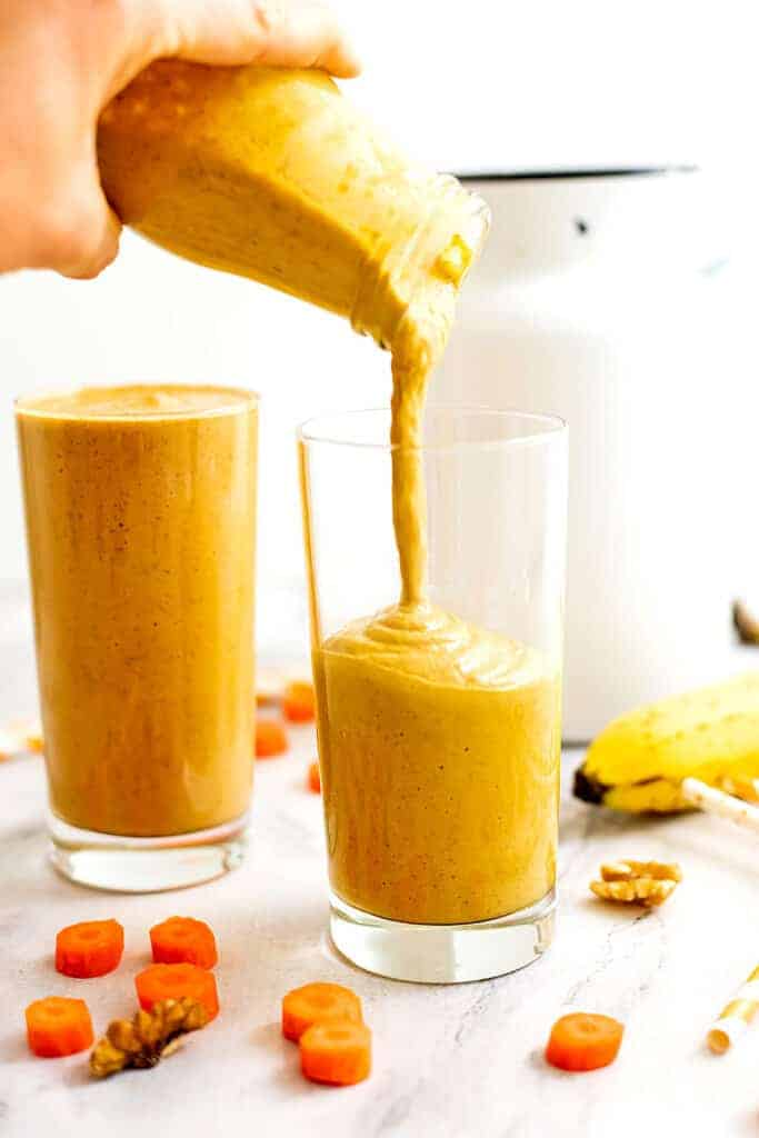 Bottle pouring carrot banana smoothie in a glass.