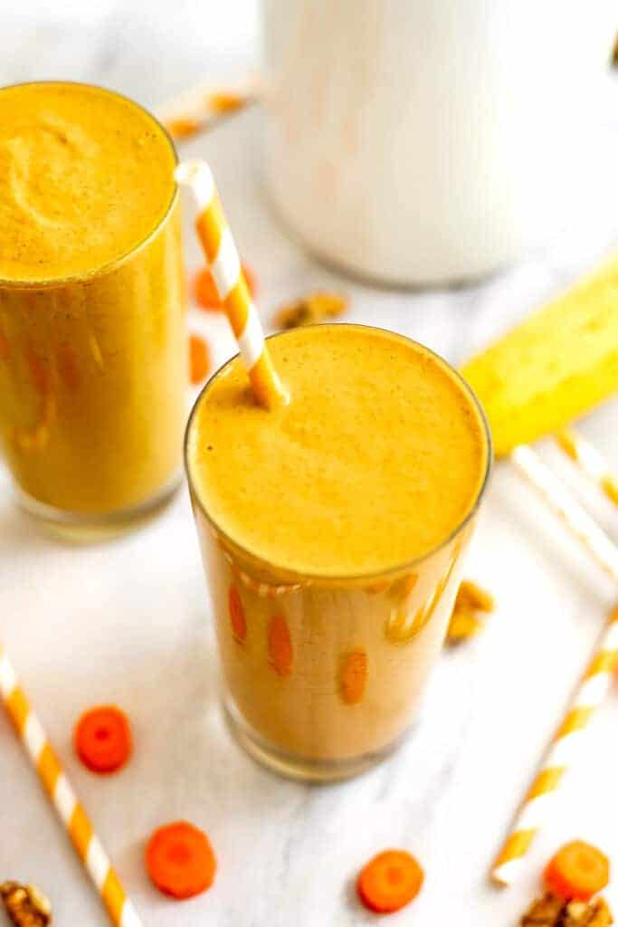 Carrot banana smoothie in a glass with orange straw.