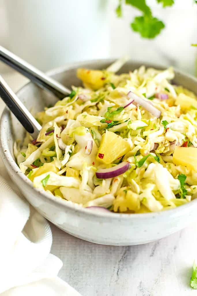 Pineapple slaw in a bowl with tongs in the bowl.