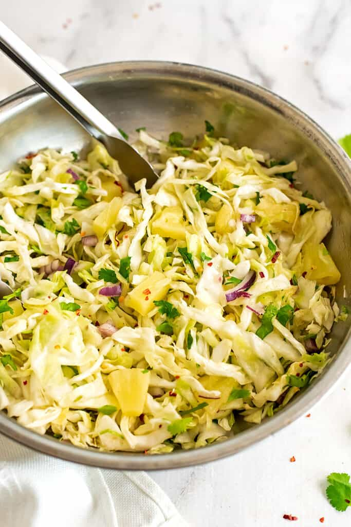 Large silver bowl filled with pineapple slaw with tongs.