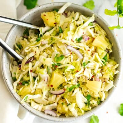 Pineapple coleslaw in a large bowl with tongs.
