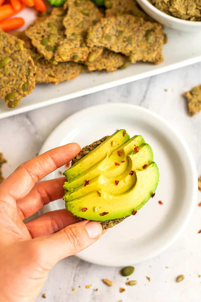 Avocado slices on a seed cracker over a plate.